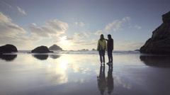 Mature, middle aged couple strolling beach on  Oregon Coast at sunset Stock Footage