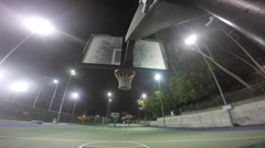 A young man playing basketball at a public park at night. Stock Footage