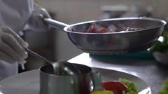 Close up of a chef ending prepare a fish dish with a drizzle of oil on his Stock Footage