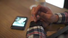 Close-up of a man using a smart watch and phone in cafe Stock Footage