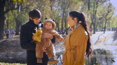 Young parents with a child in the forest standing by the pond Stock Footage