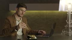 European businessman eating sushi with chopsticks Stock Footage