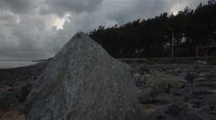 A tilt up and pan shot of sea beach and a huge rock. Stock Footage