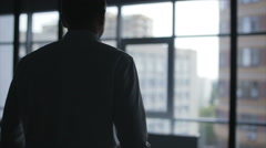 Business man puts on his jacket. Businessman dressed. Silhouette of a Stock Footage