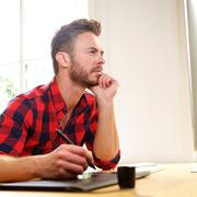 Man thinking sitting at desk with stylus Stock Photos