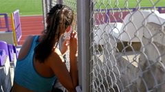Desperate disappointed track runner athlete woman holding wire netting Stock Footage