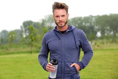 Handsome athlete standing outside in park with water bottle Stock Photos