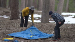 A man and woman couple packing up tent and campsite together, slow motion. Stock Footage