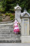Little girl in pink dress looking walking upstairs . Staircase lead to to Chr Stock Photos