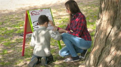 Boy and his mother draws paints on canvas and smiling Stock Footage