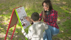 Boy and his mother draws paints on canvas and smiling. Close up. Emotions Stock Footage
