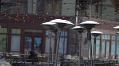 Outdoor seating and lighting on the patio outside of a restaurant at ski resort Stock Footage