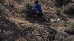 A young man trail running with his dog in a mountainous desert , slow motion. Stock Footage