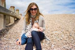 Mother with baby girl sitting on shingle beach looking at camera smiling Stock Photos