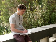 Young man outdoors, writing notes in notepad Stock Photos