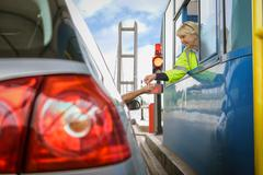 Driver in car paying at toll booth at bridge Stock Photos