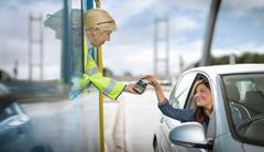 Female driver in car paying toll booth at bridge Stock Photos