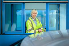 Portrait of female toll collector at toll booth on bridge Stock Photos