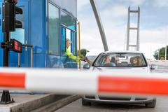 Driver in car paying toll booth at bridge Stock Photos