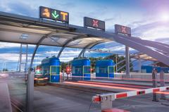 Evening view of cars passing through toll booth at bridge Stock Photos
