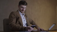 Businessman is using both his mobile nad a laptop computer Stock Footage