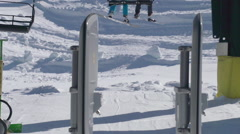 A young man snowboarder riding the chairlift up the mountain, slow motion. Stock Footage