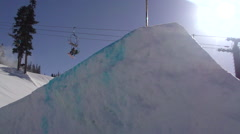 A young man snowboarder going off jumps in a terrain park, super slow motion. Stock Footage