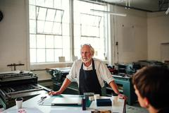 Senior craftsman/technician leading workshop in letterpress studio Stock Photos