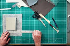 Overhead detail of hands, paper, cutting mat, ruler, scalpel and scissors in Stock Photos