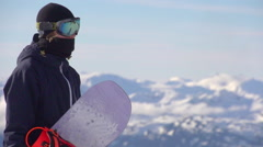 Portrait of a young man snowboarder on a scenic snow covered mountain top, super Stock Footage