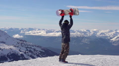 A young man snowboarder standing with his snowboard on a snow covered mountain, Stock Footage