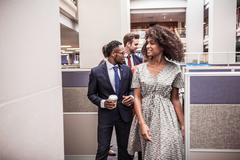 Businesswoman and men walking and talking in office Stock Photos