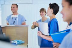 Medical staff chatting at nurses station in hospital Stock Photos