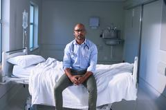 Portrait of mature male doctor sitting on hospital bed in ward Stock Photos
