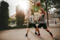 Two young men playing a game of basketball Kuvituskuvat