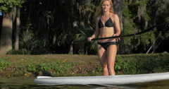 A young woman walking to the edge of a lake to go sup stand-up paddleboarding. Stock Footage