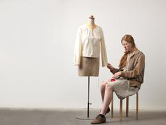 Young female fashion designer sitting on stool pinning blouse on dressmaker's Stock Photos