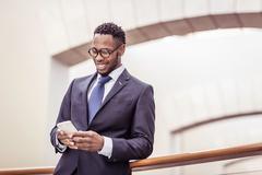 Businessman reading smartphone update on office balcony Stock Photos