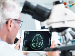 Doctor viewing a MRI brain scan on digital tablet in a laboratory Stock Photos