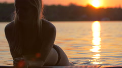 A young woman sitting on her sup stand-up paddleboard on a lake at sunset. Stock Footage