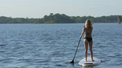 A young woman sup stand-up paddleboarding on a lake. Stock Footage