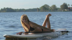 A young woman sitting on her board while sup stand-up paddleboarding on a lake. Stock Footage