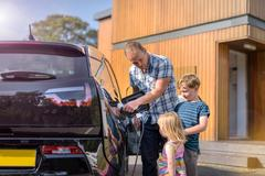 Father with children, charging electric car Stock Photos