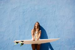 Happy surfer girl with surfboard in front of blue wall Stock Photos