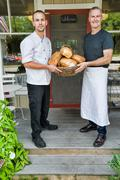 Cafe owner and chef with basket of bread in front of restaurant Kuvituskuvat