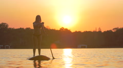 A young woman sup stand-up paddleboarding on a lake at sunset. Stock Footage