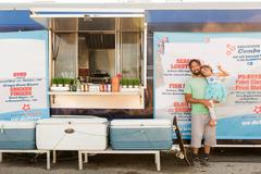 Portrait of father and daughter standing beside fast food trailer Stock Photos