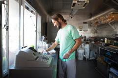 Man preparing food for customer in fast food trailer Stock Photos