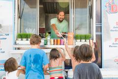 Group of children queuing at fast food trailer Stock Photos