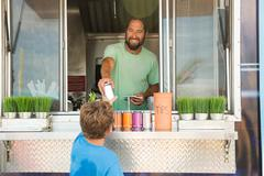 Man in fast food trailer passing drink to boy through hatch Stock Photos